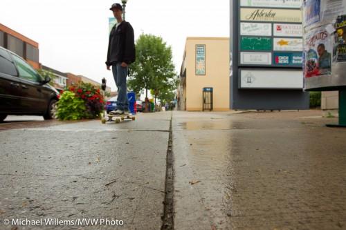 Skateboarder on wet sidewalk